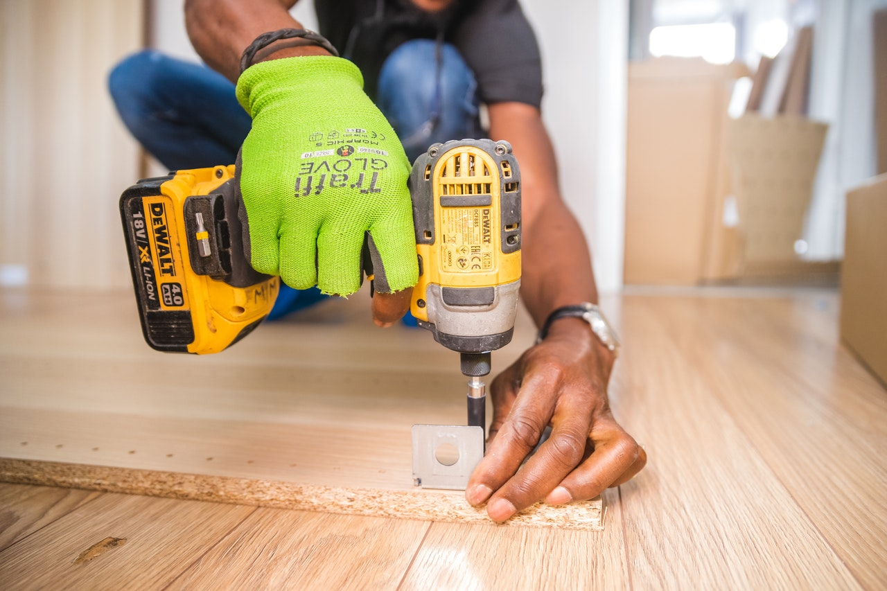 person-using-dewalt-cordless-impact-driver-on-brown-board-1249611